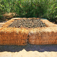 A compost bin made with bales of hay